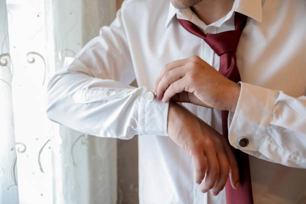 A businessman buckles a shirt button stock photo