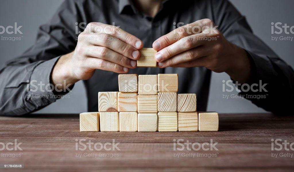 Bau einer Pyramide von Holzpflaster Geschäftsmann. Konzept der Unternehmenshierarchie und Geschäftsstrategie. – Foto