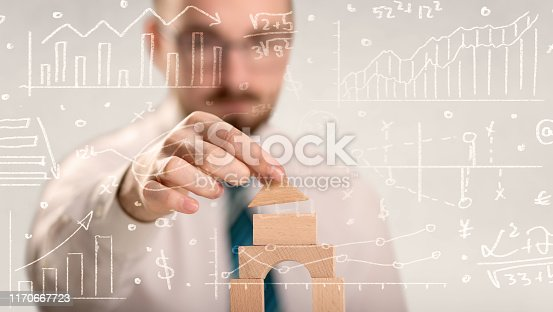 452598975 istock photo Businessman building a tower 1170667723