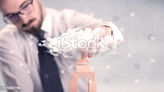 452598975 istock photo Businessman building a tower 1170667766