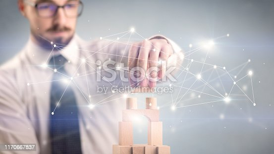 452598975 istock photo Businessman building a tower 1170667837
