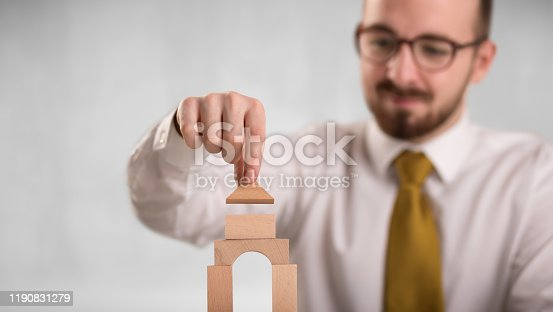 452598975 istock photo Businessman building a tower 1190831279