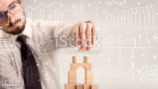 452598975 istock photo Businessman building a tower 1190831877
