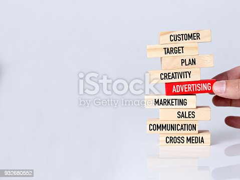 istock Businessman Building ADVERTISING Concept with Wooden Blocks 932680552