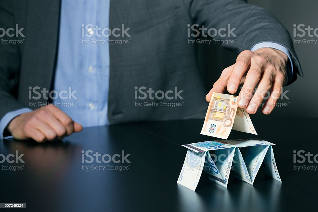 businessman building financial pyramid from euro money stock photo