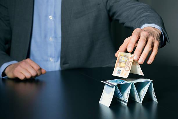 hombre de negocios edificio financiera pirámide de dinero euro - conspiración fotografías e imágenes de stock