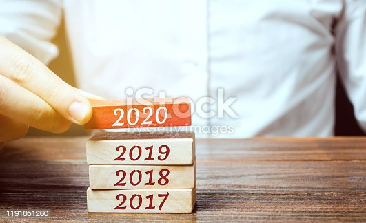 619522908istockphoto Businessman builds wooden blocks 2020. The concept of the beginning of the new year. New goals. Next decade. Trends and changes in the world. Build plans and planning. Time report 1191051260