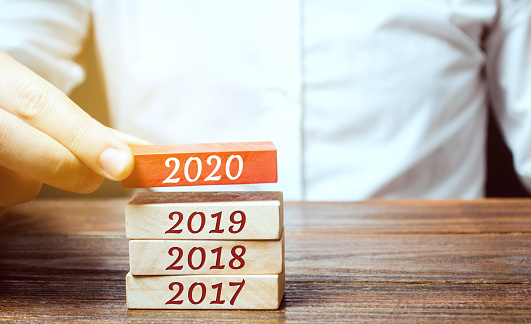 619522908 istock photo Businessman builds wooden blocks 2020. The concept of the beginning of the new year. New goals. Next decade. Trends and changes in the world. Build plans and planning. Time report 1191051260