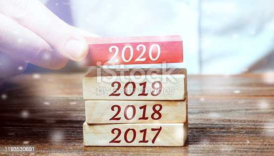 897726248 istock photo Businessman builds wooden blocks 2020. The concept of the beginning of the new year. New goals. Next decade. Trends and changes in the world. Build plans and planning. Time report. Snow, snowfall 1193530691