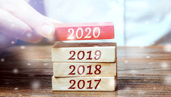 619522908 istock photo Businessman builds wooden blocks 2020. The concept of the beginning of the new year. New goals. Next decade. Trends and changes in the world. Build plans and planning. Time report. Snow, snowfall 1193530691