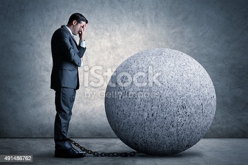 A standing businessman with head in hand tied down by the proverbial ball and chain.
