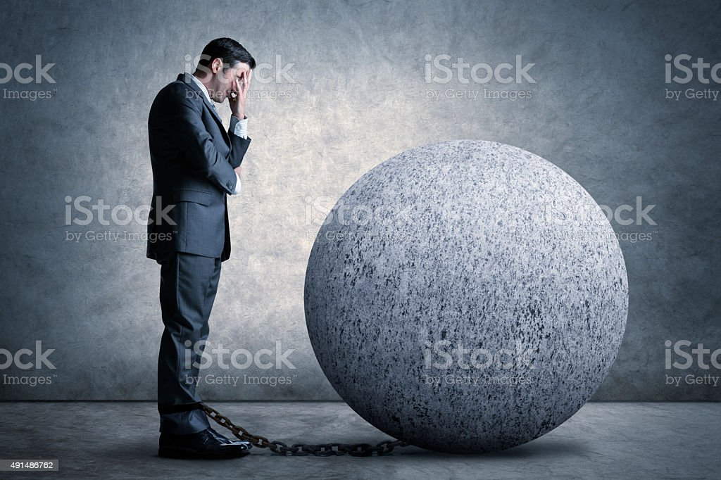 Businessman Burdened By A Ball And Chain stock photo