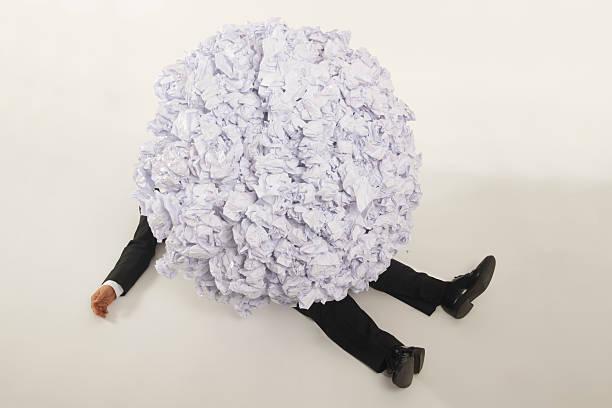 businessman buried under pile of paperwork - gömülü stok fotoğraflar ve resimler