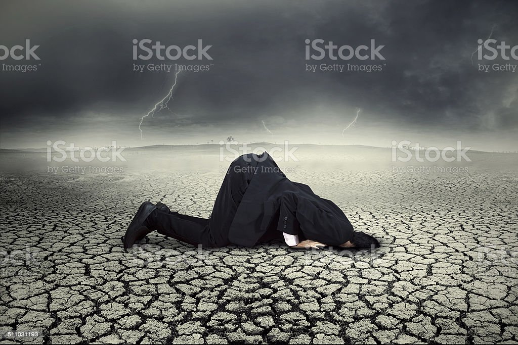 Businessman burying his head in the land stock photo