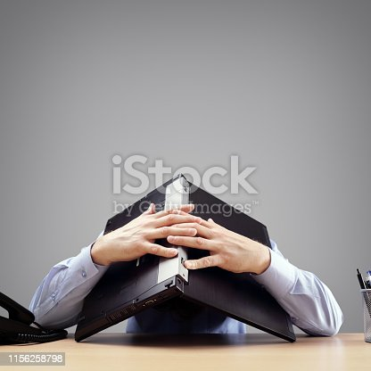 istock Businessman burying his head under a laptop computer asking for help 1156258798