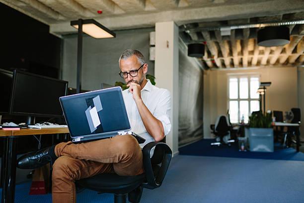 businessman busy working on laptop - alvarez stock-fotos und bilder