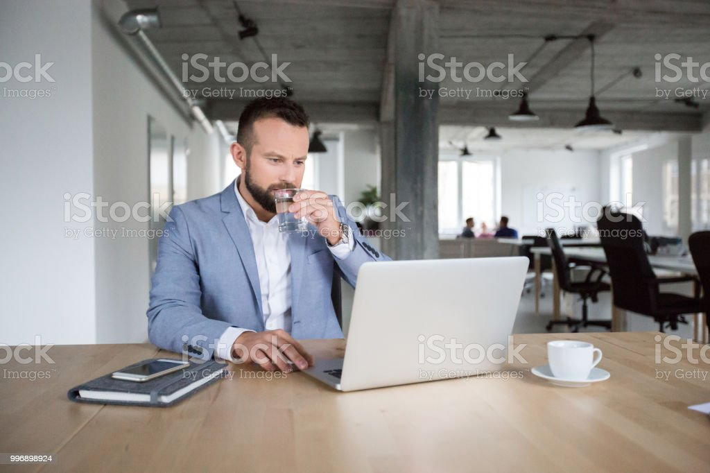 Businessman busy working on laptop Businessman working on laptop and drinking water in office Adult Stock Photo
