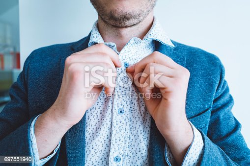 516141885istockphoto Businessman buttoning his shirt 697551940