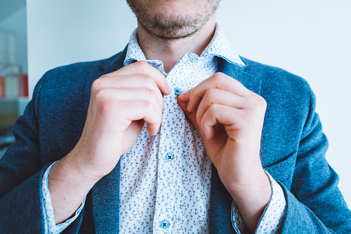 516141885 istock photo Businessman buttoning his shirt 697551940