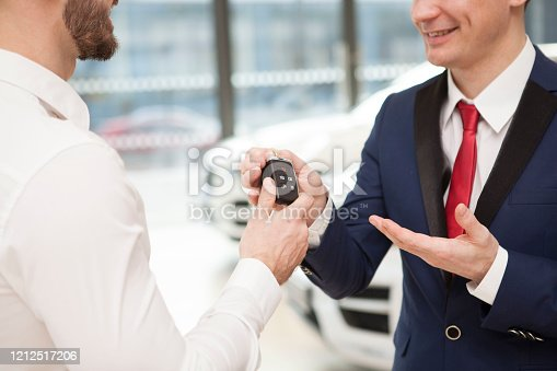 1049198210 istock photo Businessman buying new car at the dealership 1212517206