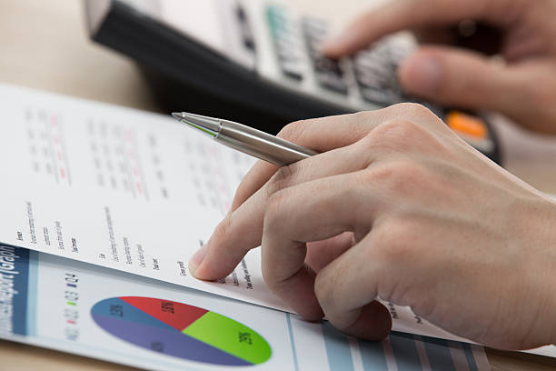 Businessman calculating and checking articles of agreement Businessman calculating and checking articles of agreement expense stock pictures, royalty-free photos & images