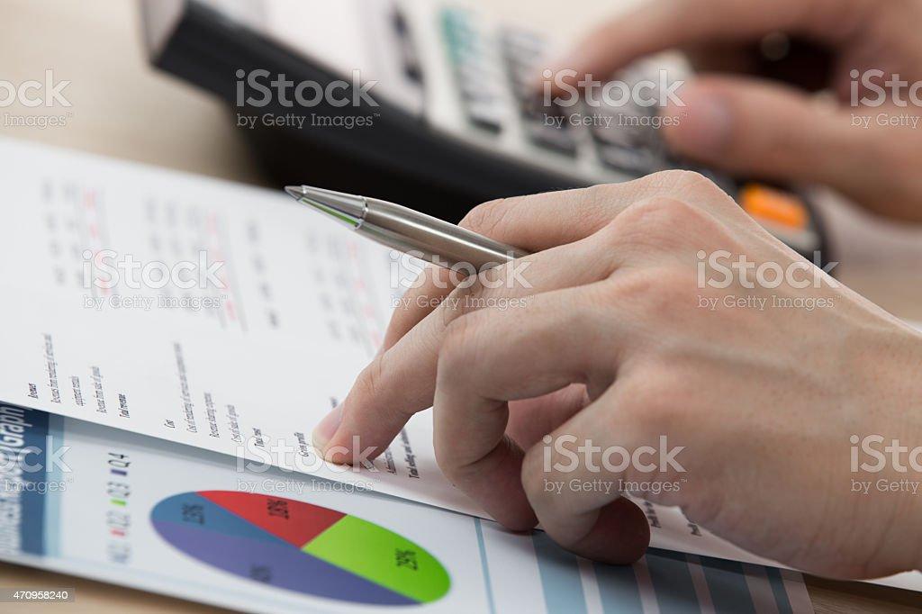 Uomo d'affari il calcolo e leggere articoli del Contratto - foto stock
