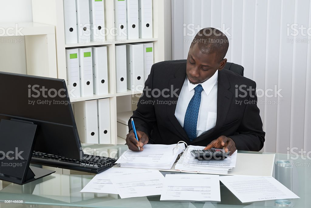 Businessman Calculating Finance Bills stock photo