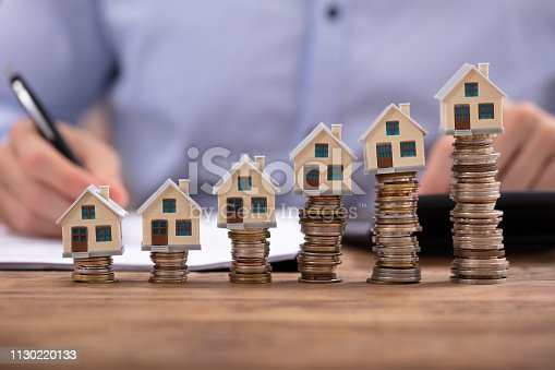 Midsection Of Businessman Calculating Invoice With House Models Arranged On Stacked Coins