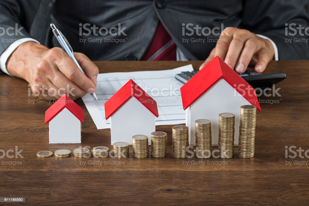 Businessman Calculating Tax By House Models And Coins stock photo