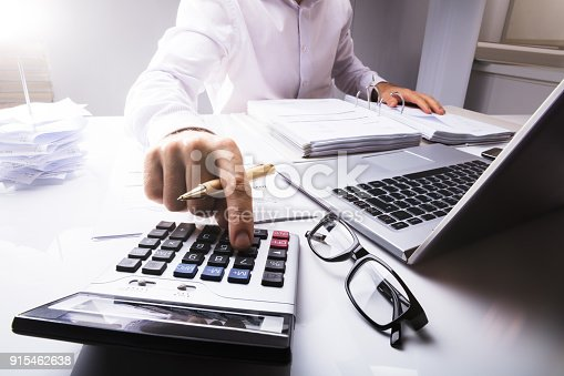 istock Businessman Calculating Tax Using Calculator 915462638