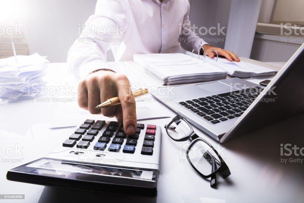 Businessman Calculating Tax Using Calculator stock photo