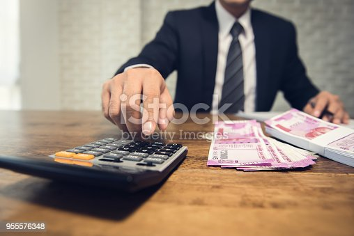 istock Businessman calculating the conversion rate for the indian rupee money 955576348