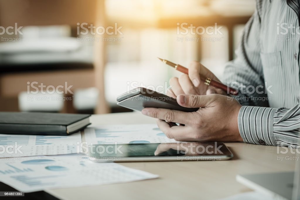 Businessman calculation and holding calculator analysis summary report with tablet. royalty-free stock photo