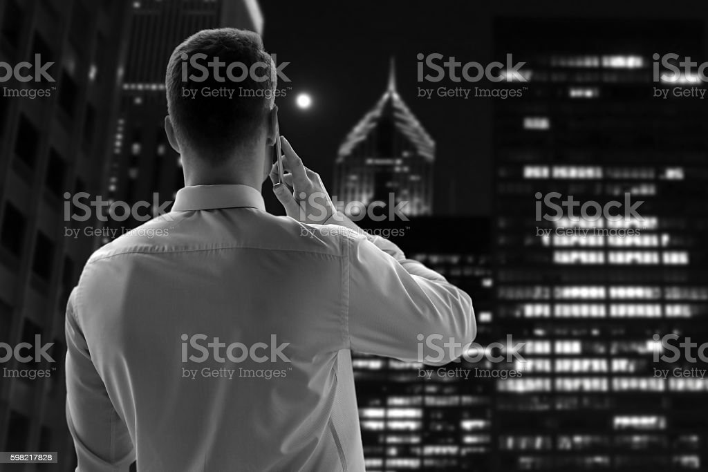 businessman calling on phone over office near with window. Night foto royalty-free