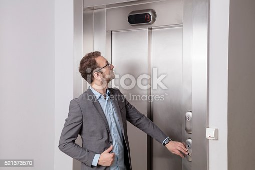 638591126 istock photo Businessman calling the elevator 521373570