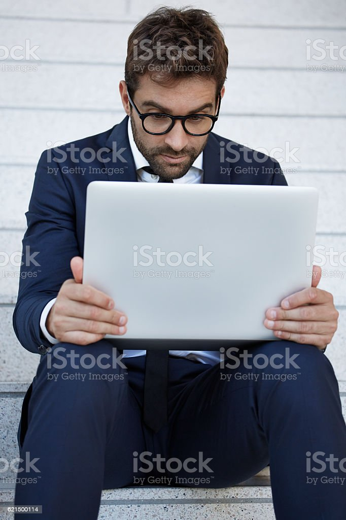 Businessman can't believe what he sees on laptop photo libre de droits