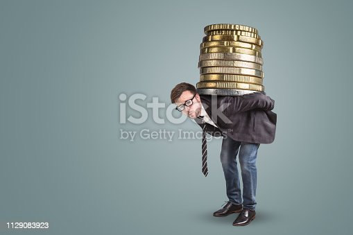 A young businessman with an overstrained expression his face is holding an oversized stack of coins on the back.