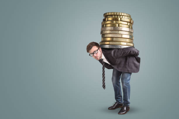 Businessman carrying a giant stack of coins on his back A young businessman with an overstrained expression his face is holding an oversized stack of coins on the back. fee stock pictures, royalty-free photos & images