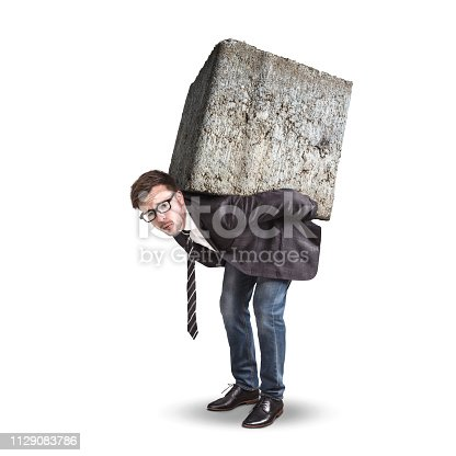 A young businessman is burdened with a giant stone on his back. Conceptual image representing pressure and stress. Isolated on a white background.