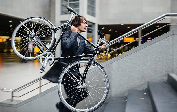 geschäftsmann, die mit dem fahrrad auf seiner schulter - fahrradträger stock-fotos und bilder