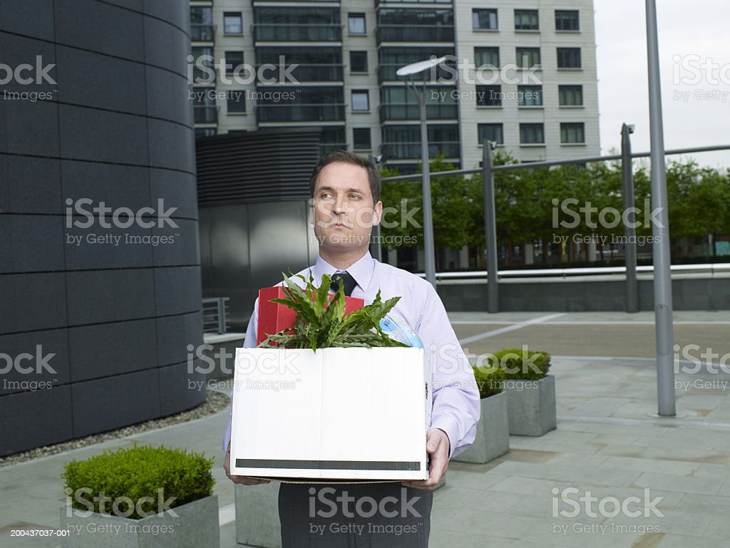 Businessman carrying box containing plant and files on street stock photo
