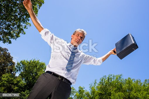 istock Businessman carrying briefcase against sky 690367950