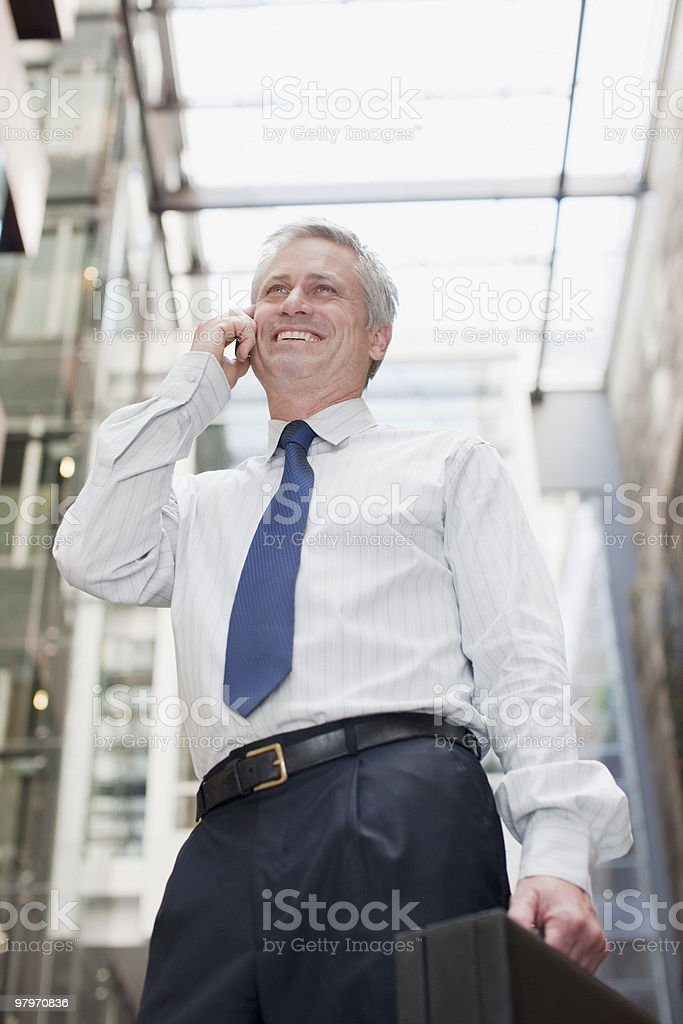 Businessman carrying briefcase and talking on cell phone royalty-free stock photo