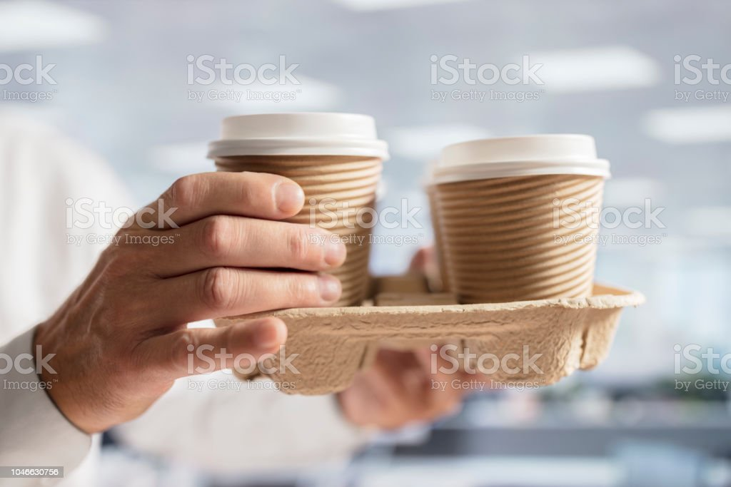 Businessman carrying coffee take out disposable cups in office for meeting stock photo