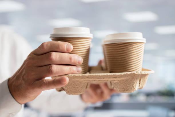 businessman carrying coffee take out disposable cups in office for meeting - karton zbiornik zdjęcia i obrazy z banku zdjęć