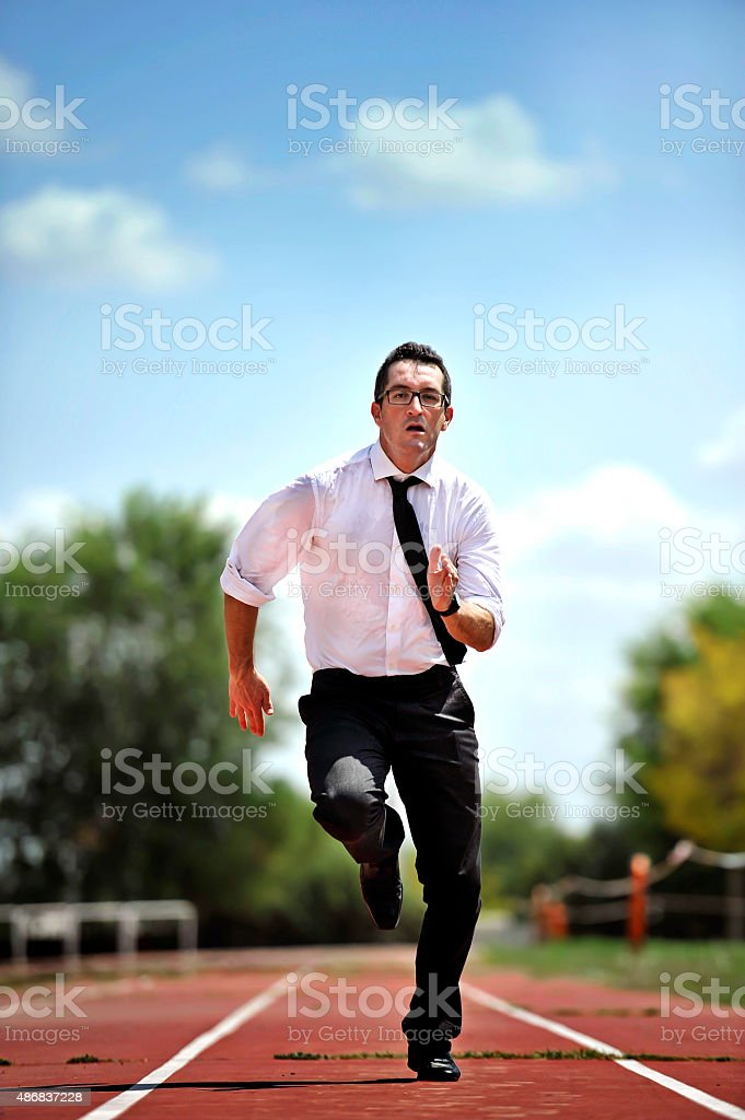 businessman carrying folder running desperate in stress on athletic track stock photo
