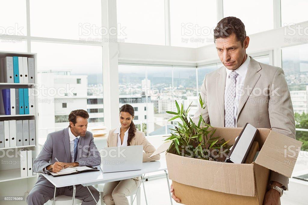 Businessman carrying his belongings in box stock photo