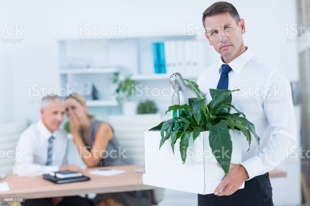 Businessman carrying his belongings with colleagues behind stock photo