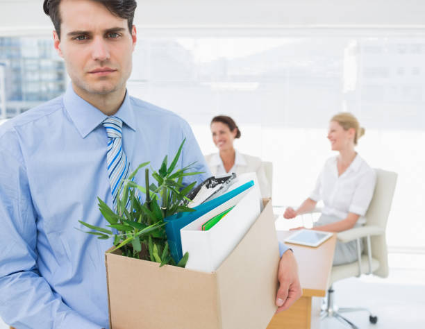 businessman carrying his belongings with colleagues in background - leaving partnership corporate business sitting stock photos and pictures