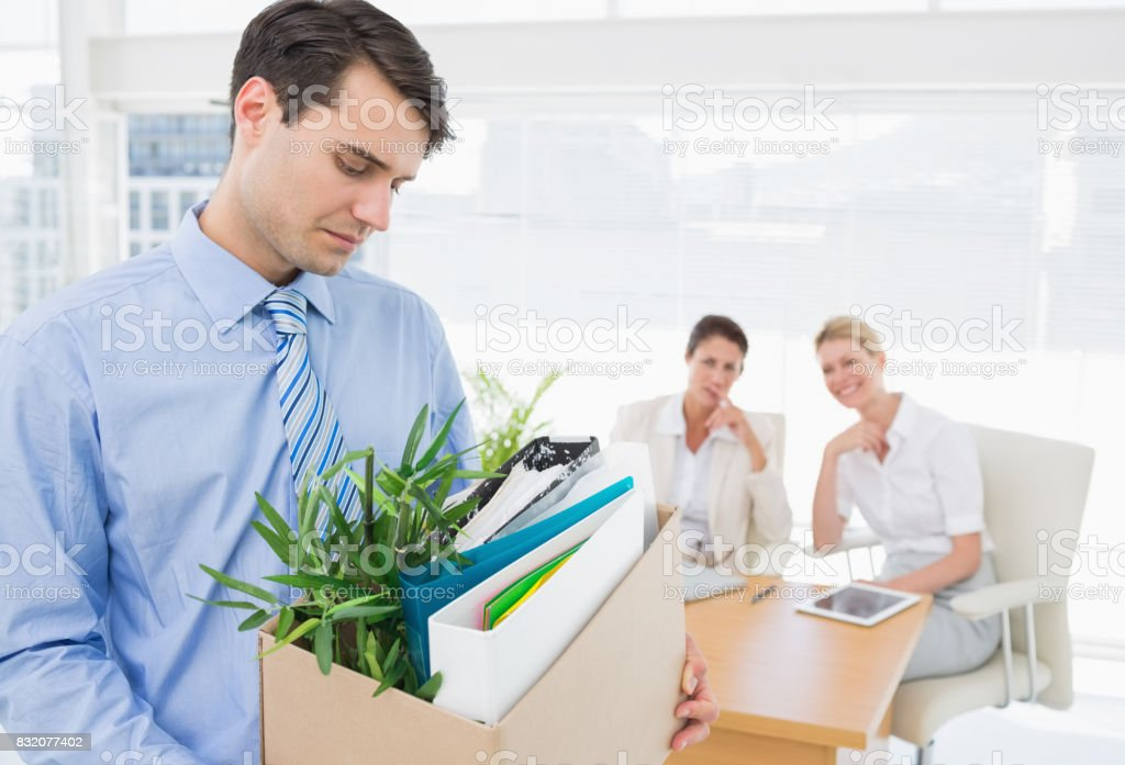Businessman carrying his belongings with colleagues in background stock photo